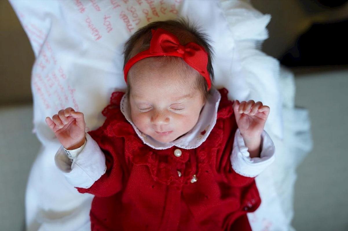 A menina veste um macacão vermelho, com uma tiara na cabeça